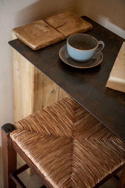 Winter suite, teacup on top of wood and steel table with wooden stools.